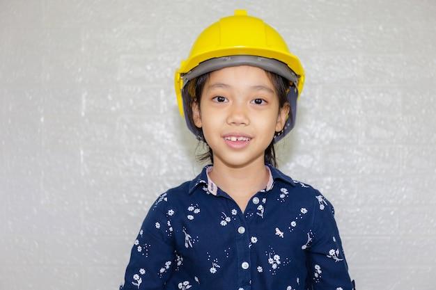 Conceito de carreira dos sonhos, retrato de garoto feliz engenheiro com capacete olhando para a câmera no fundo desfocado