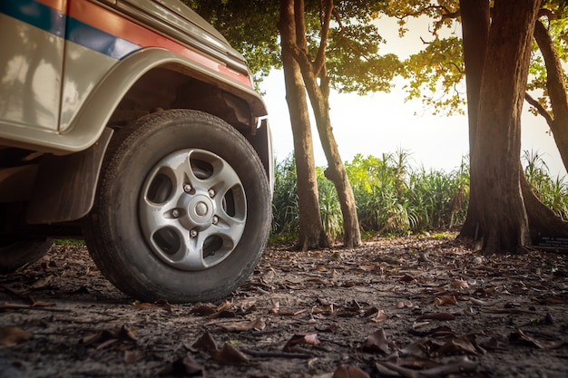 Conceito de carro 4x4 com grande roda offroad. polícia turística de carros brancos nos bosques da ilha de havelock, nas ilhas andaman e nicobar, na índia