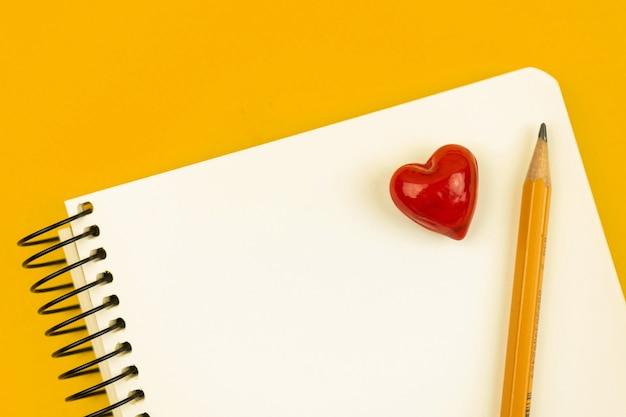 Conceito de carta de amor escolar com bloco de notas e lápis, coração vermelho em papel branco, foto de vista de topo de mesa amarela com espaço de cópia