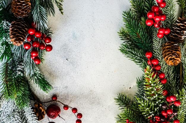 Conceito de cartão de natal - moldura feita com galhos de árvores perenes com neve e decoração de bugigangas em fundo de pedra com espaço de cópia