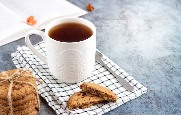 Conceito de casa aconchegante - livro aberto, xícara de chá e biscoitos com pedaços de chocolate em um guardanapo xadrez