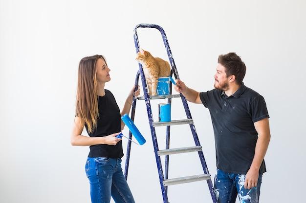 Conceito de casal de reparação, renovação, animal de estimação e amor - família jovem com gato fazendo reparos e pintando paredes juntos e rindo.