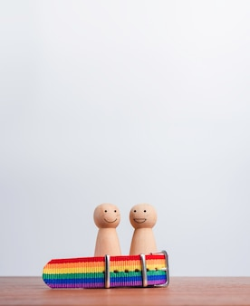 Conceito de casal lgbt. duas figuras de madeira com sorrisos felizes juntos na bandeira do arco-íris, pulseira na mesa de madeira e fundo com espaço de cópia, estilo vertical. símbolo do orgulho lgbt.