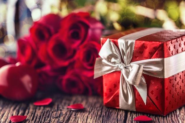 Conceito de casamento do dia dos namorados. bouquet de rosas e presente embrulhado com corações vermelhos na mesa de madeira.