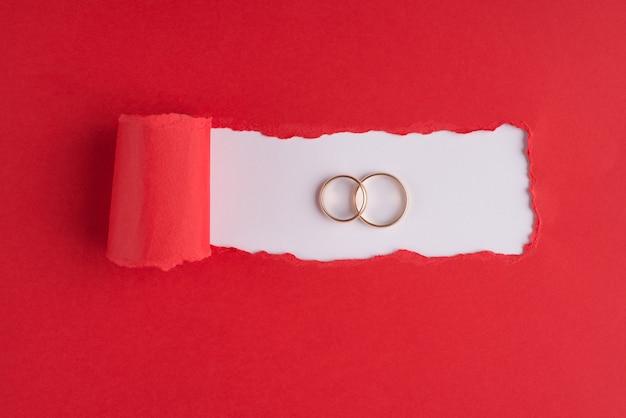 Conceito de casamento. foto de visão aérea superior de dois anéis de tamanhos diferentes em papel vermelho rasgado sobre fundo branco com copyspace
