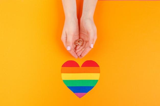 Conceito de casamento gay com bandeira do arco-íris e anéis