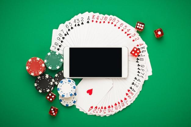 Conceito de casino online com cartas de jogar, fichas de dados e smartphone