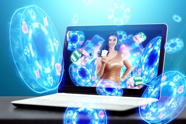 Conceito de casino online, jogos de azar, jogos de dinheiro online, apostas. fichas de casino neon voam para fora do laptop, uma linda garota tem cartas nas mãos, dados.