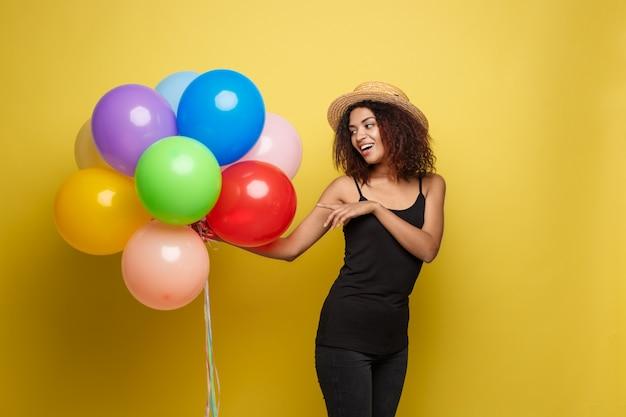 Conceito de celebração - close up retrato feliz jovem mulher africana bonita em t-shirt preto sorrindo com balão de festa colorida. fundo amarelo do estúdio pastel.