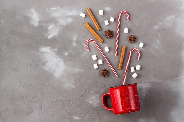 Conceito de celebração da bebida de natal. xícara com marshmallows de anis, canela e bengala de doce na mesa cinza