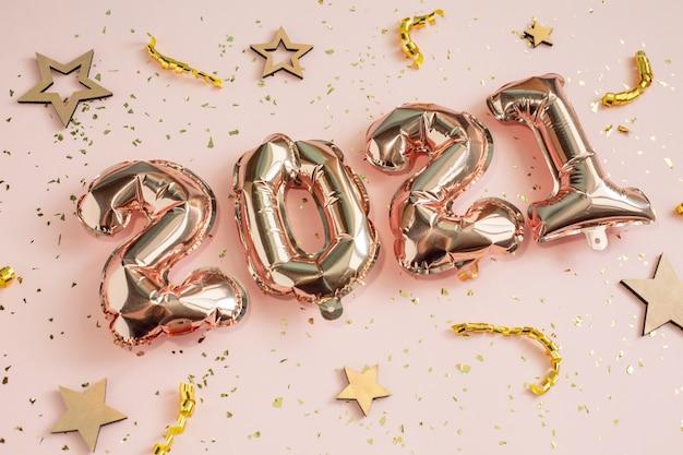 Conceito de celebração de ano novo e natal 2021. balões de folha em forma de números 2021 e confetes. balões de ar. decoração de festa de férias.
