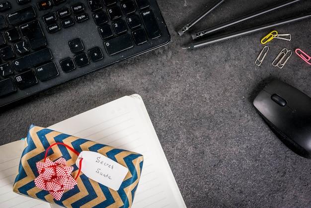 Conceito de celebração de natal do escritório, a idéia de compartilhar presentes secreta santa teclado, mouse, caderno, canetas, lápis