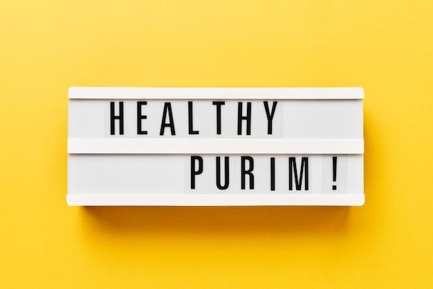 Conceito de celebração do purim. purim saudável escrito em uma caixa de luz em um amarelo. vista superior, copie o espaço.