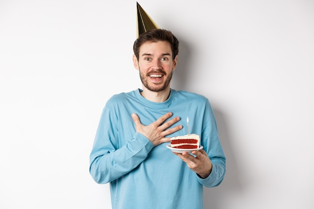 Conceito de celebração e feriados. aniversariante surpreso com chapéu de festa, segurando o bolo de aniversário e parecendo grato, em pé sobre um fundo branco.