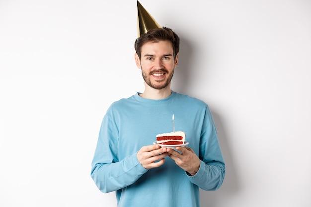 Conceito de celebração e feriados. jovem feliz com chapéu de festa, comemorando o aniversário, segurando o bolo de aniversário e sorrindo, em pé sobre um fundo branco.