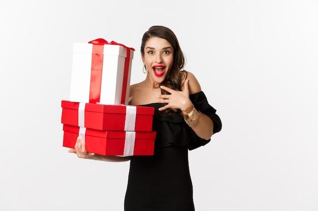 Conceito de celebração e férias de natal. mulher animada e feliz recebe presentes, segurando presentes de natal e regozijando-se, em um vestido preto sobre fundo branco.