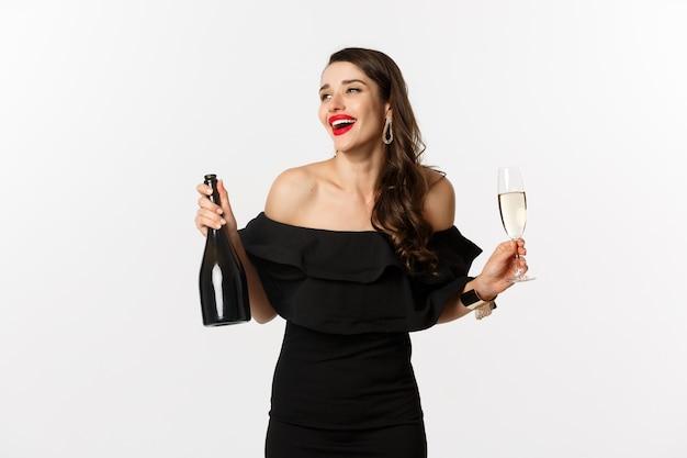 Conceito de celebração e festa. mulher morena elegante com vestido glamour, segurando a garrafa e a taça de champanhe, se divertindo no feriado de ano novo.