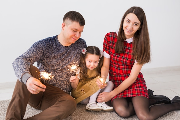 Conceito de celebração, família, ano novo, natal e feriados - pais felizes e a filha com estrelinhas sentadas no tapete sobre a parede cinza