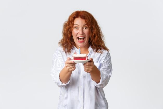 Conceito de celebração, feriados e emoções. mulher de meia-idade ruiva animada e otimista aproveitando a festa em sua homenagem, segurando o bolo de aniversário com uma vela acesa, fazendo o pedido de aniversário.