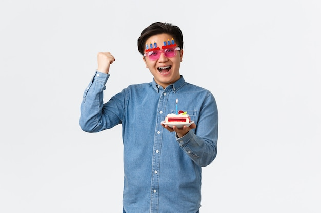 Conceito de celebração, feriados e estilo de vida. cara asiático positivo otimista em óculos de sol de festa engraçada, segurando o bolo de aniversário e a bomba de punho em gesto de hooray, determinado desejo de aniversário em realidade.