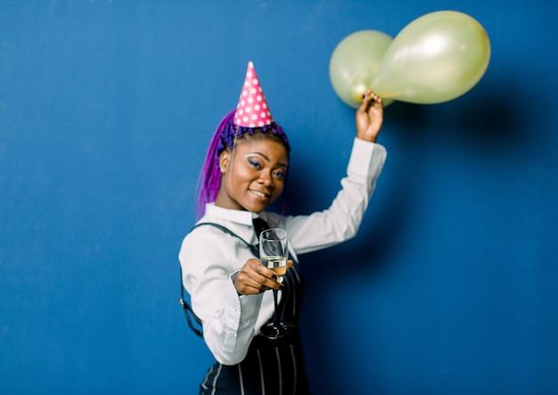 Conceito de celebração, festa de aniversário - close-up retrato feliz mulher africana bonita jovem em calças pretas e saia branca, sorrindo com balão colorido partido amarelo. espaço de estúdio azul pastel.