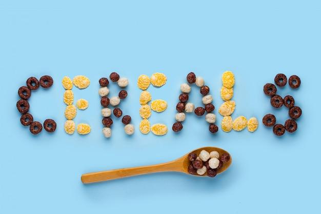 Conceito de cereais. colher com vidros, bolas de chocolate, anéis e flocos de milho para um café da manhã seco e saudável em uma superfície azul