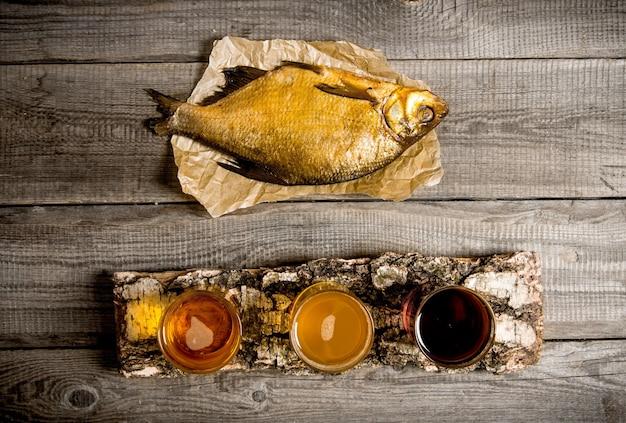 Conceito de cerveja. peixe defumado e três cervejas frescas em bétula ficam na mesa de madeira. vista do topo