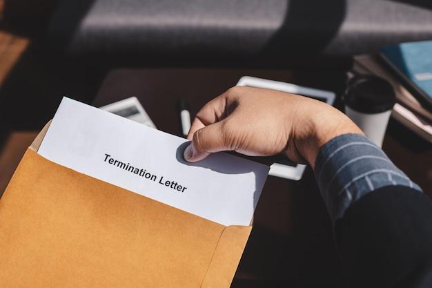 Conceito de cessação de emprego e demissão, empresário segurando o formulário de rescisão de emprego