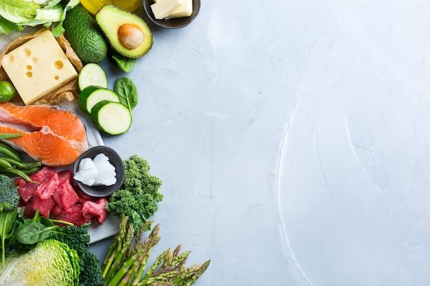 Conceito de ceto de nutrição de dieta equilibrada. variedade de ingredientes alimentares saudáveis de baixo teor de carboidratos cetogênicos para cozinhar na mesa da cozinha. vegetais verdes, carne, salmão, queijo, ovos