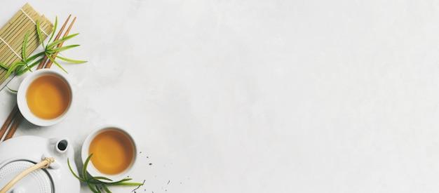 Conceito de chá asiático, duas xícaras brancas de chá, bule, jogo de chá, pauzinhos, esteira de bambu, cercada com chá verde seco no fundo branco