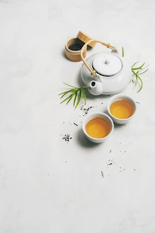 Conceito de chá asiático, duas xícaras de chá brancas, bule, jogo de chá, pauzinhos, esteira de bambu