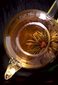 Conceito de chá, bule com chá rodeado de fundo de madeira, cerimônia do chá, chá verde em uma xícara transparente