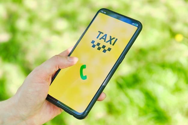 Conceito de chamada de táxi através do aplicativo em um smartphone, segurando uma mão.