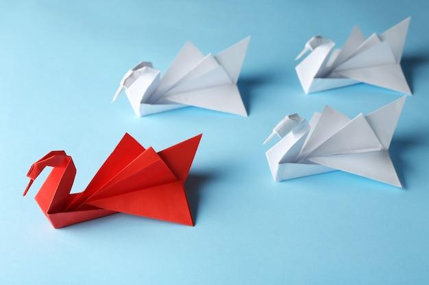 Conceito de chefe vs líder. pássaros de origami branco atrás do vermelho em fundo azul