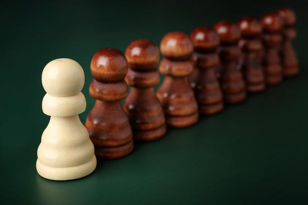 Conceito de chefe vs líder. peças de xadrez em fundo verde