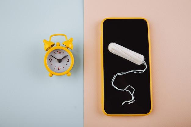 Conceito de ciclo menstrual. despertador amarelo e tela do smartphone com tampão de algodão.