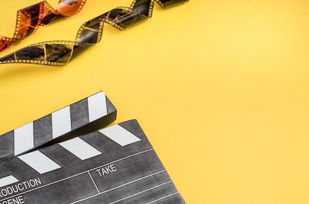 Conceito de cinema - claquete com pipoca e tira de filme em fundo amarelo com espaço de cópia.