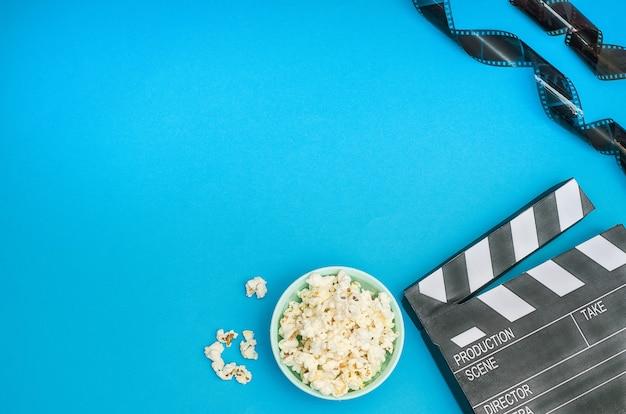 Conceito de cinema - claquete com pipoca e tira de filme sobre fundo azul com espaço de cópia.