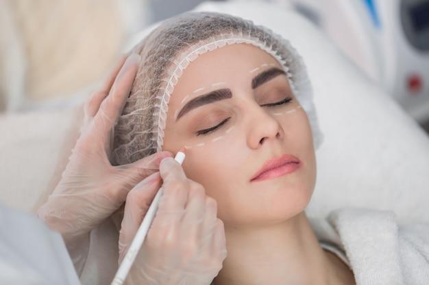Conceito de cirurgia plástica. mãos nas luvas, marcando o rosto das mulheres