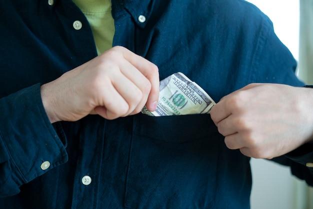 Conceito de cleptomania, homem criminoso roubando coisas e colocá-las no bolso