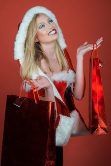 Conceito de clima de celebração e ano novo. menina feliz com conceito de venda e compra de sacola de compras vermelha