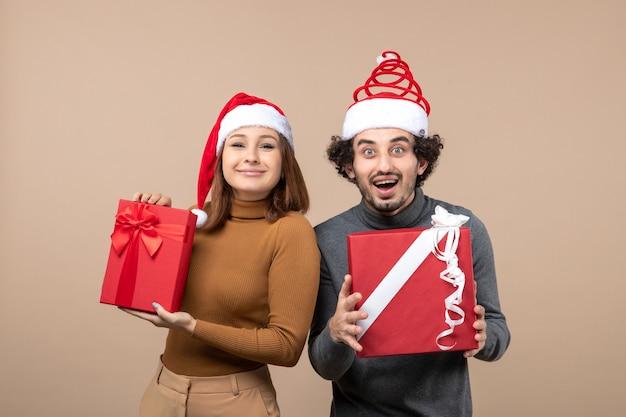 Conceito de clima e festa de ano novo - jovem casal feliz e animado segurando presentes usando chapéus de papai noel em cinza