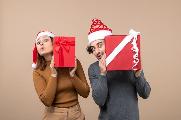 Conceito de clima e festa de ano novo - jovem e animado casal segurando presentes com chapéus de papai noel
