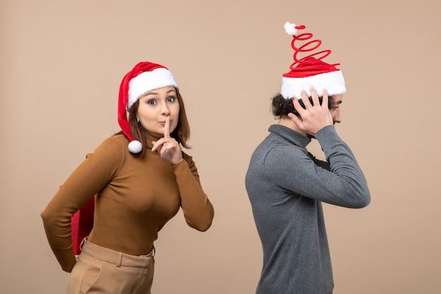 Conceito de clima festivo de ano novo com casal adorável e engraçado usando chapéus vermelhos de papai noel, garota fazendo surpresa