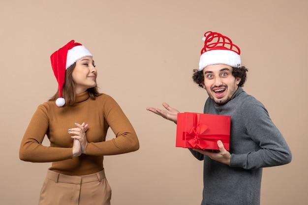 Conceito de clima festivo de ano novo com casal adorável engraçado usando chapéus vermelhos de papai noel. a garota deu seu presente em cinza