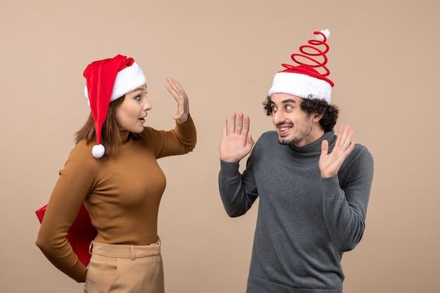 Conceito de clima festivo de ano novo com casal adorável engraçado usando chapéus vermelhos de papai noel, menina escondendo o presente atrás em cinza