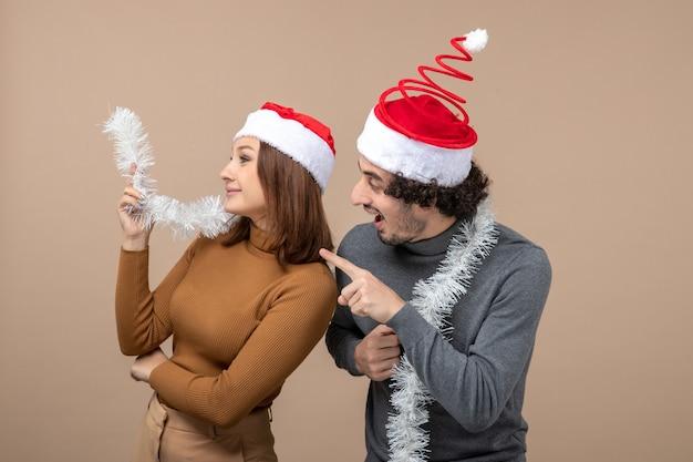 Conceito de clima festivo de ano novo com casal adorável satisfeito e animado usando chapéu de papai noel vermelho na cor cinza