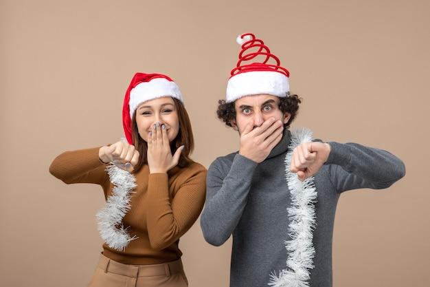 Conceito de clima festivo de ano novo com casal adorável satisfeito e animado, usando chapéus vermelhos de papai noel, se divertindo juntos no cinza