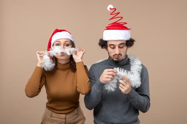 Conceito de clima festivo de ano novo com casal adorável satisfeito e animado usando chapéus vermelhos de papai noel