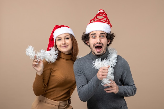 Conceito de clima festivo de ano novo com lindo casal adorável usando chapéu de papai noel vermelho na imagem cinza
